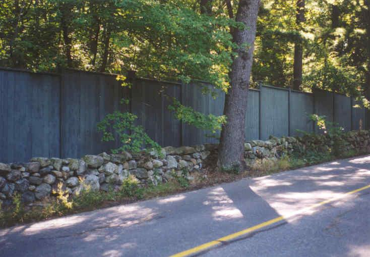 Short Rock Wall in Front of Wood Fence with Tree